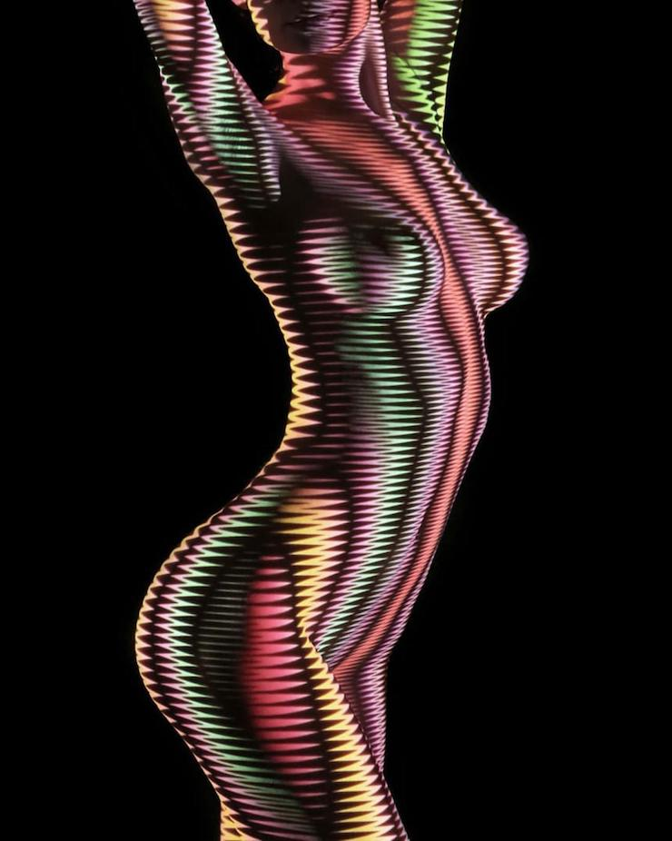 Un photographe habille des femmes dévêtues d'ombres et lumière colorée