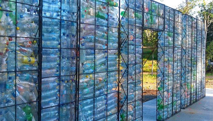 Un homme construit des maisons faites de bouteilles en plastique qui ressemblent à des maisons ordinaires