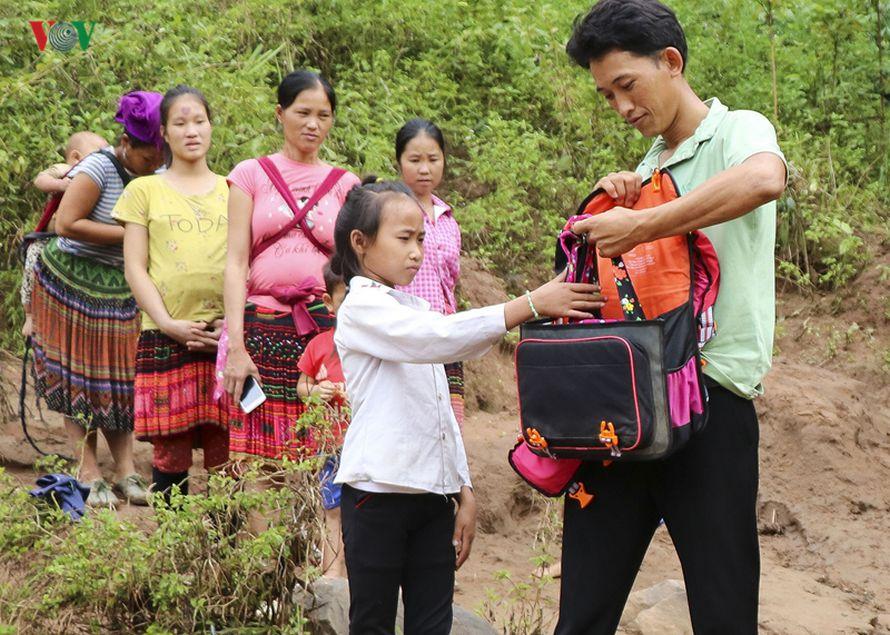Des enfants dans un village au Vietnam traversent la rivière dans des sacs en plastique pour aller à l'école