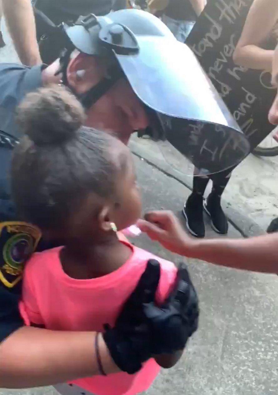 Un policier réconforte une fillette en larmes qui lui a demandé s'il allait lui tirer dessus