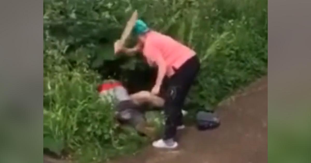 Une femme en colère utilise une planche de bois pour taper les fesses nues d'un couple qui fait l'amour dans un buisson